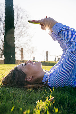 Happy woman using mobile phone while lying on grass during sunny day - p300m2264389 by Andrés Benitez