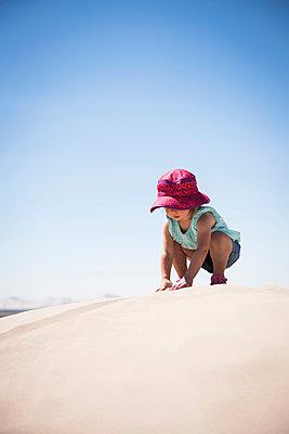 Female toddler crouching on top of sand dune, Little Sahara, Utah, USA - p429m1407840 by Mike Tittel