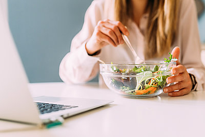 Italy, Woman eating salad and looking at laptop - p924m2283059 by Eugenio Marongiu