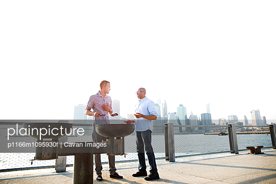 Man and father standing by barbecue grills at promenade in city against clear sky - p1166m1095930f by Cavan Images