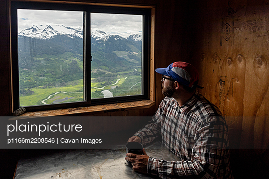 Bearded man in checkered shirt and cap sitting at table with mug of hot beverage and looking at mountains while resting in cozy cabin in British Columbia, Canada - p1166m2208546 by Cavan Images