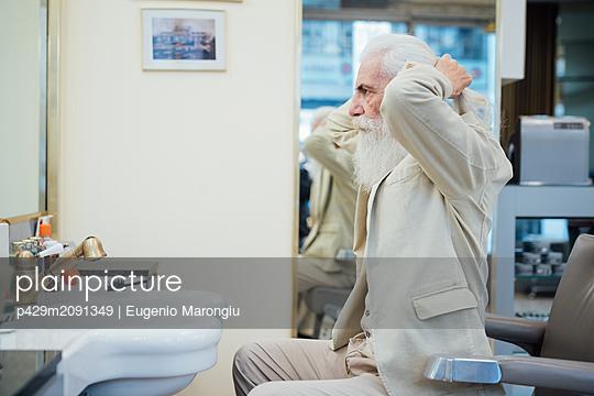 Senior businessman tying hair in salon - p429m2091349 by Eugenio Marongiu