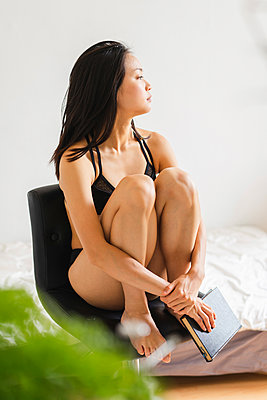 Attractive young woman in lingerie sitting on chair at home with book - p300m2059814 von VITTA GALLERY