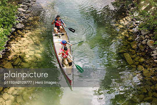 Overhead view of father canoeing with two sons in river - p1192m2129777 by Hero Images