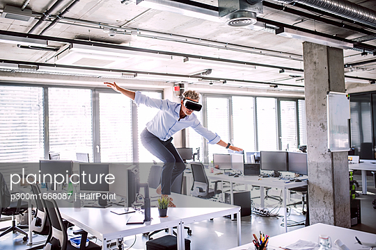 Barefoot mature businessman on desk in office wearing VR glasses - p300m1568087 by HalfPoint