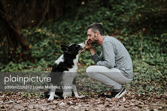 Man playing with dog while crouching at public park - p300m2226312 by Gala Martínez López
