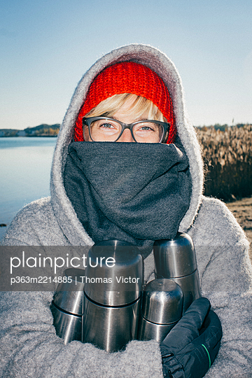 Woman in warm clothing holding thermos flasks - p363m2214885 by Thomas Victor