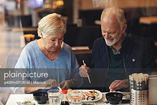 Senior couple eating food while sitting in restaurant - p426m2213246 by Maskot