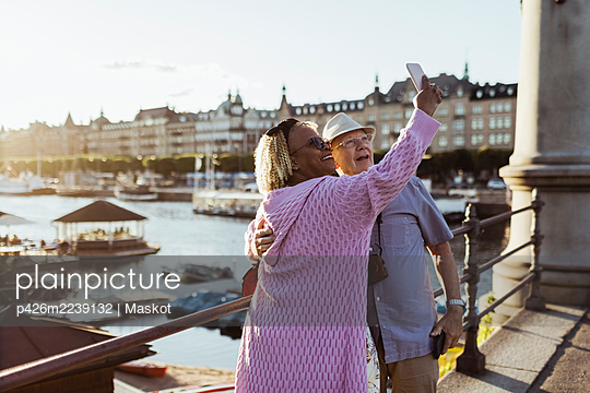 Smiling senior couple taking selfie while standing on bridge against lake in city - p426m2239132 by Maskot
