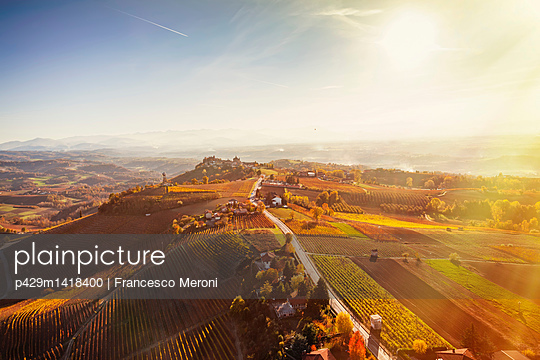 Sunlit view from hot air balloon of rolling landscape and autumn vineyards, Langhe, Piedmont, Italy - p429m1418400 by Francesco Meroni