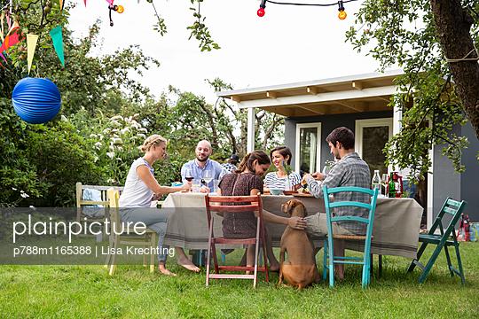 Freunde feiern eine Gartenparty - p788m1165388 von Lisa Krechting