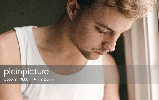 Young man by window - p956m1136867 by Anna Quinn