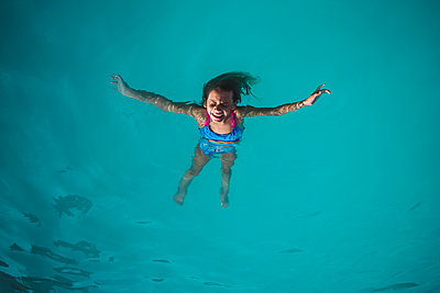 High angle view of carefree girl floating on water in swimming pool - p1166m1489886 by Cavan Images