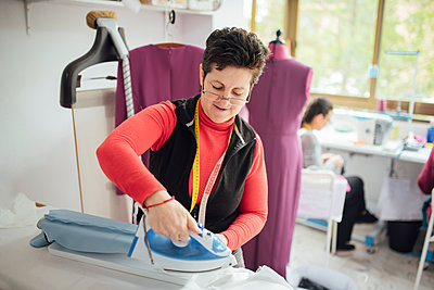 senior woman with glasses ironing a dress in a fashion design studio - p1166m2130992 by Cavan Images