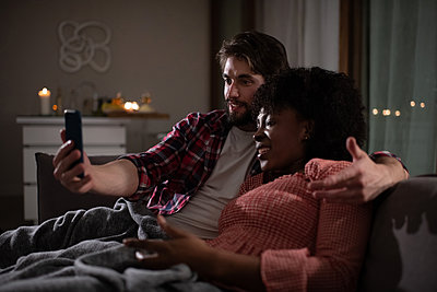 Multiracial couple talking with parents online - p1166m2193868 by Cavan Images