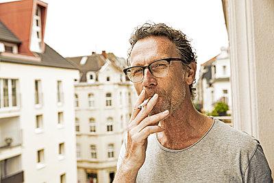 Portrait of man smoking on balcony - p300m1157290 by Jo Kirchherr