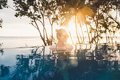 Woman in infinity pool at sunset, Nai Thon Beach, Phuket, Thailand - p300m2166377 by Christophe Papke