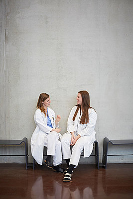 Full length of smiling female doctors talking while sitting against wall at hospital - p426m2018946 by Maskot