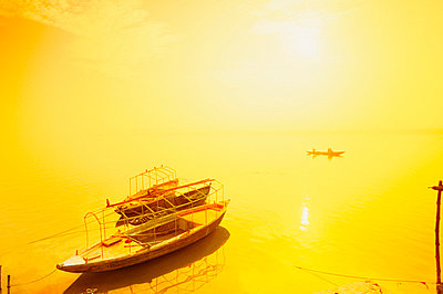 Sun shining on a boat on the Ganges river, India - p4425704f by Design Pics