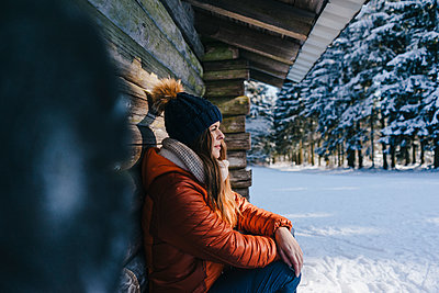 Young woman in winter clothing at log cabinpe - p586m2005081 by Kniel Synnatzschke