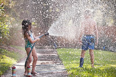 Children playing with water hose on sidewalk - p924m1125606f by Kinzie Riehm