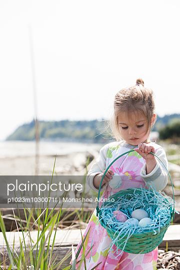Girl gathering Easter eggs in basket on beach