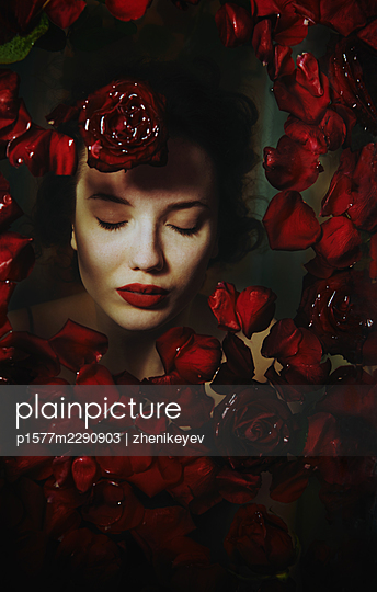 Woman taking a bath with rose petals - p1577m2290903 by zhenikeyev