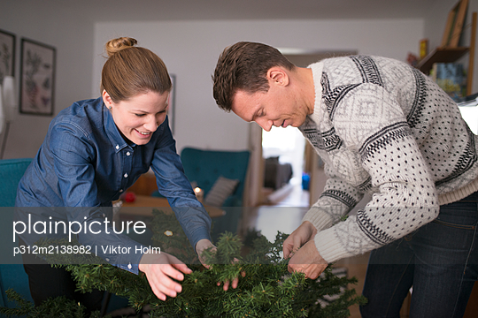Couple preparing Christmas tree - p312m2138982 by Viktor Holm