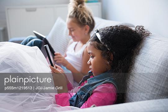 Girls using digital tablets on sofa - p555m1219513 by JGI/Jamie Grill