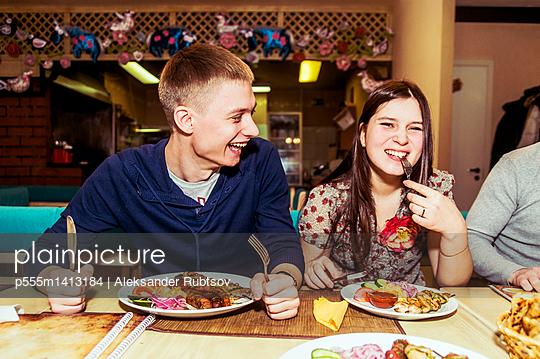 Caucasian couple laughing in restaurant - p555m1413184 by Aleksander Rubtsov