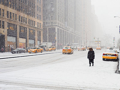Man walking in a city in the snow during a blizzard, yellow taxis on the street. - p1100m1045539f by Chris Corradino