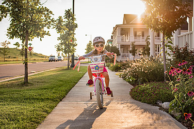 Playful girl wearing sunglasses while riding bicycle - p1166m1509637 by Cavan Images