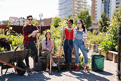 Portrait confident friends in sunny, urban community garden - p1192m2130192 by Hero Images