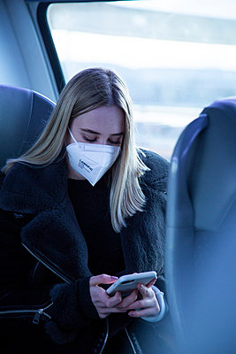 Young woman with FFP2 mask using smartphone in the train - p1650m2285228 by Hanna Sachau