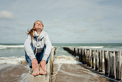 Woman sitting on fence at the beach, relaxing at the sea - p300m2023617 by Kniel Synnatzschke