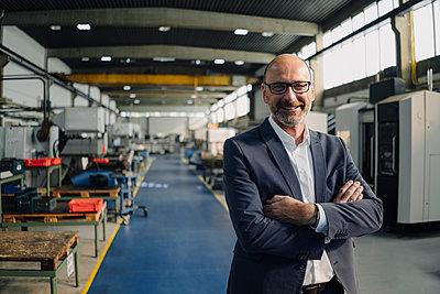Portrait of a smiling businessman in a factory - p300m2170423 by Kniel Synnatzschke