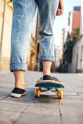 Young female skate boarder on her skateboard, partial view - p300m949768f by Bonninstudio