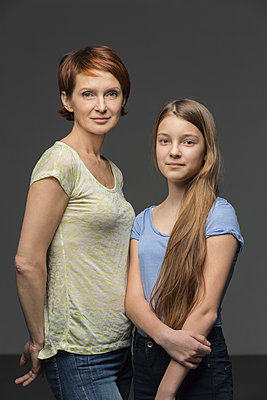Portrait of mother and daughter standing against gray background - p301m1130787f by Vladimir Godnik