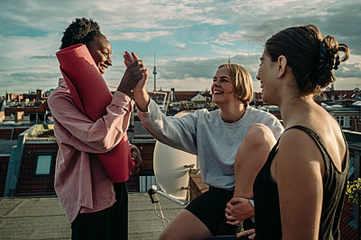 Smiling female with exercise mat giving high-five to friend after yoga on rooftop during sunrise - p426m2233505 by Maskot