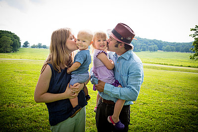 Mid adult couple kissing daughter and baby son on cheek in rural field - p924m1480536 by Zave Smith