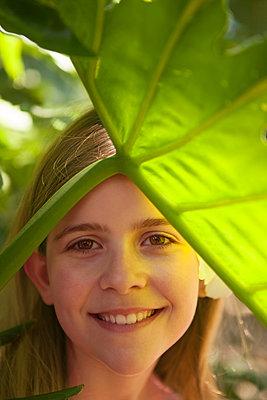 Mädchen Portrait unter grünem Blatt - p045m1425009 von Jasmin Sander
