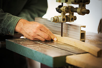A craftsman using a machine drill on a piece of smooth planed shaped wood.  - p1100m1522486 by Mint Images