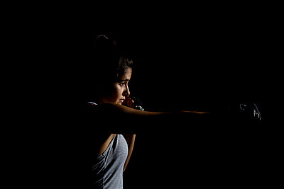 Portrait with black background of woman in gym with boxing gloves - p1166m2123614 by Cavan Images