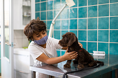 Boy wearing face mask while cleaning puppy at home - p300m2221720 by Valentina Barreto