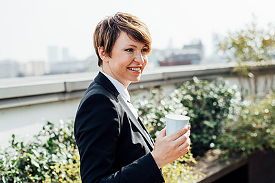 Smiling female entrepreneur holding disposable coffee cup while looking away - p300m2275709 by Eugenio Marongiu