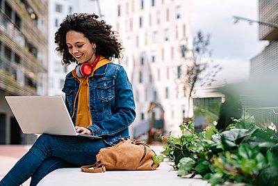 Curly hair woman using laptop while sitting on bench - p300m2282061 by COROIMAGE
