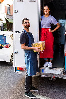Full length portrait of confident young multi-ethnic colleagues standing at food truck in city - p426m2046524 by Maskot