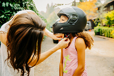 Mother fastening helmet on daughter - p555m1306246 by Inti St Clair