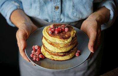 Close up of Caucasian woman holding plate of pancakes - p555m1523090 by Valeriya Tikhonova
