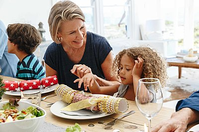 Woman talking to granddaughter playing with Christmas cracker at dining table - p924m2138534 by Image Source